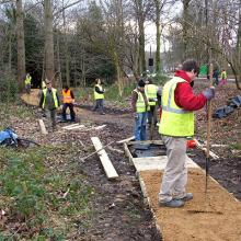 Volunteers in park repairing decking footpath