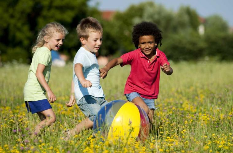 photo of 1girl and 2 boys playing with a ball in a field