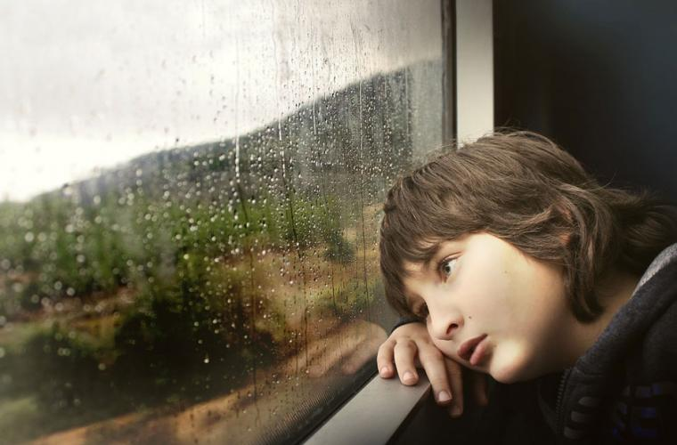 Boy looking out a rainy window