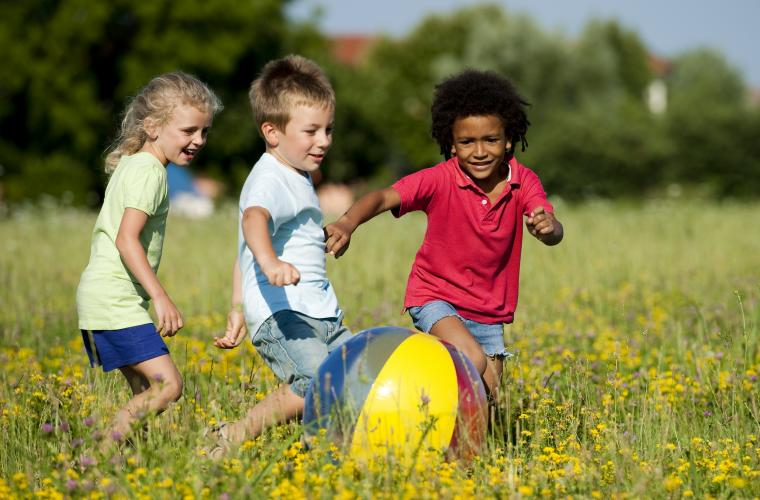 Three children playing in a field