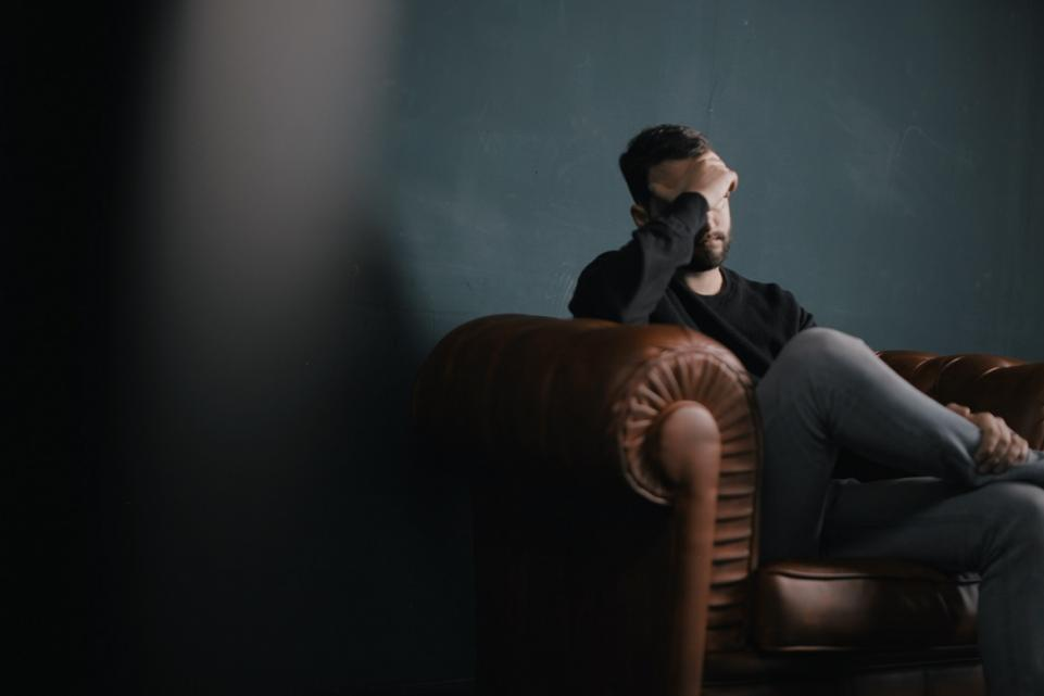 Man sitting on a couch, looking stressed
