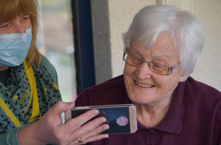 Carer in mask shares image on her phone with elderly lady